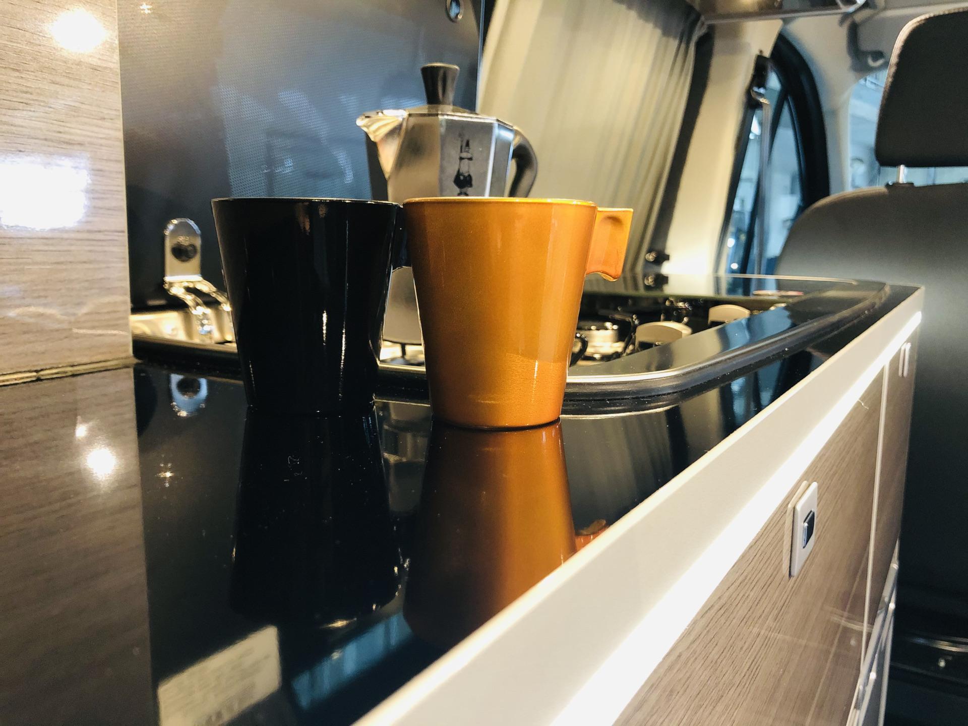 Arbeitsfläche und Kochfeld im Campingbus mit Espresootassen und Espresso-Kocher.