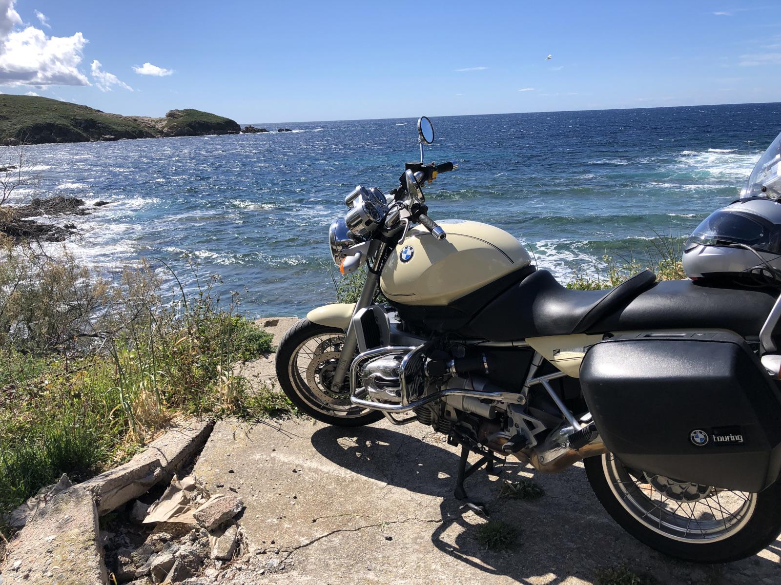 Motorrad an sonniger Felsenküste auf der Insel Korsika.