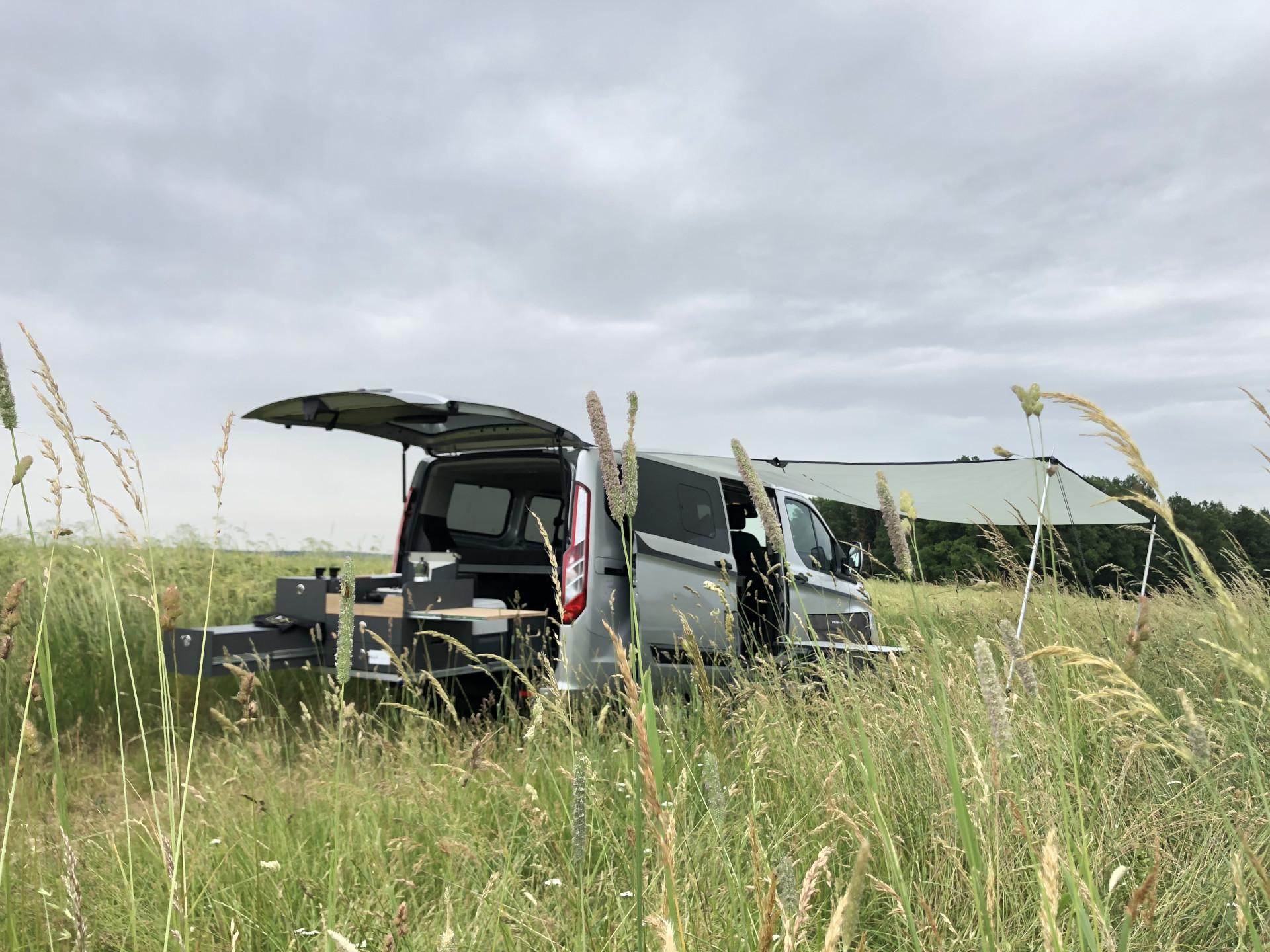 Der Campingbus steht auf sommerlicher Blumenwiese.