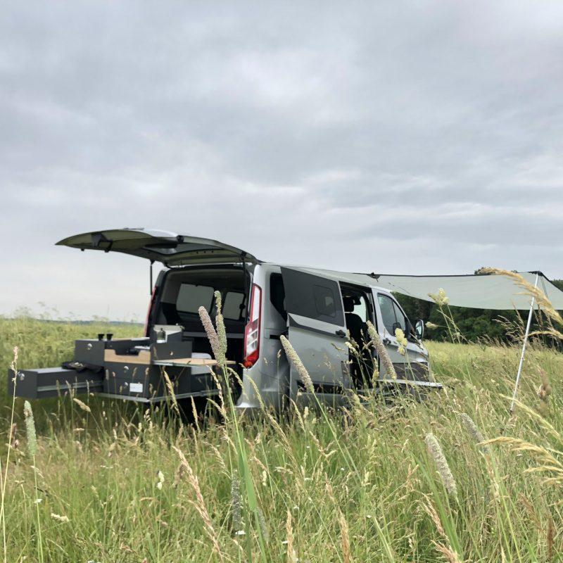 Voll ausgestatteter Camper zwischen sommerlichen Feldern.