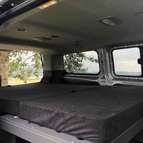 Aufgebautes Bett im Innenraum.