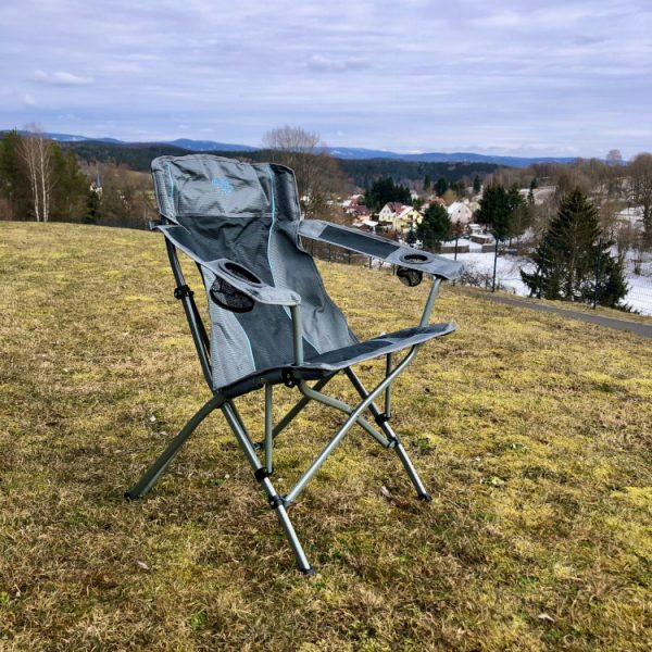 Campingstuhl in der warmen Frühlingssonne auf einer grünen Wiese unter blauem Himmel.