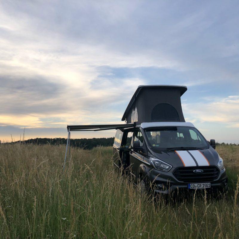 Camping Bus mit Aufstelldach und Markise im Getreidefeld.