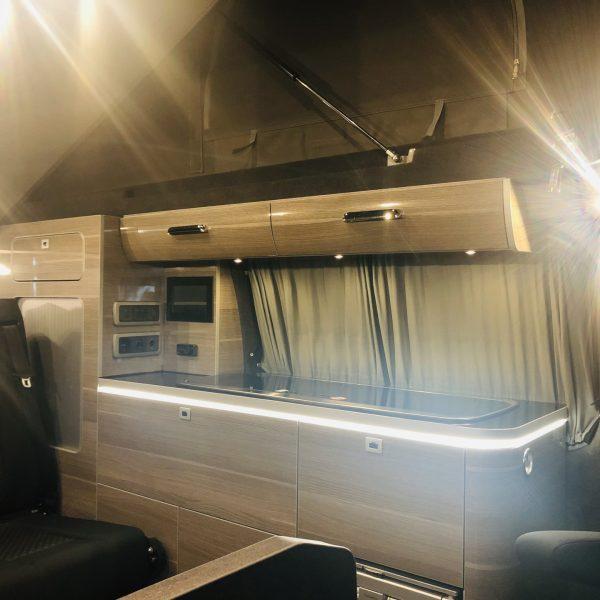 Blick auf die Küchenzeile im Camper-Van und in das aufgestellte Hochdach.
